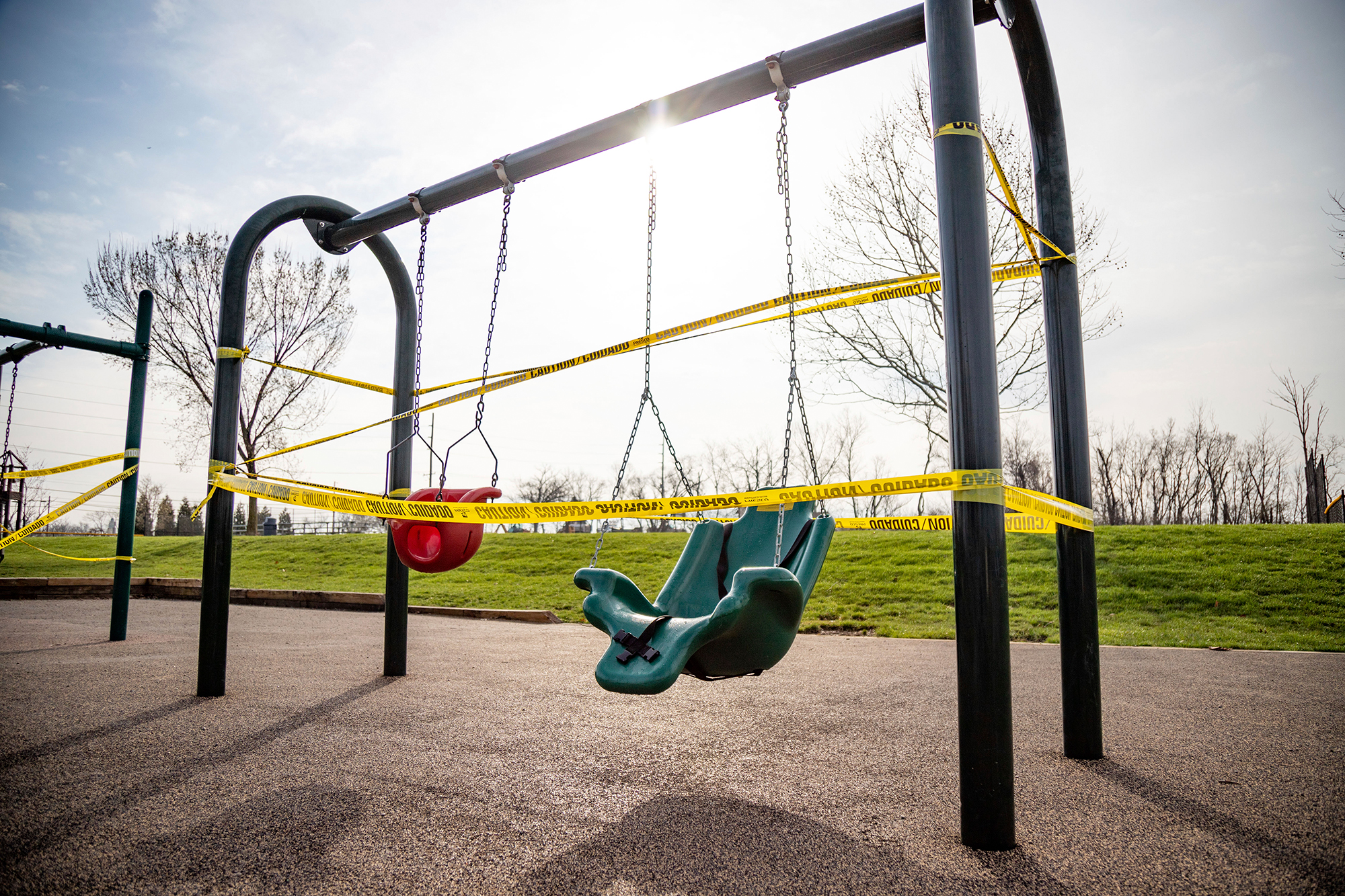 Playground equipment is cordoned off with yellow caution tape at the Veteran's Memorial Park on Harrison Avenue in Cincinnati, Ohio, in the wake of the coronavirus pandemic on Thursday, March 24.