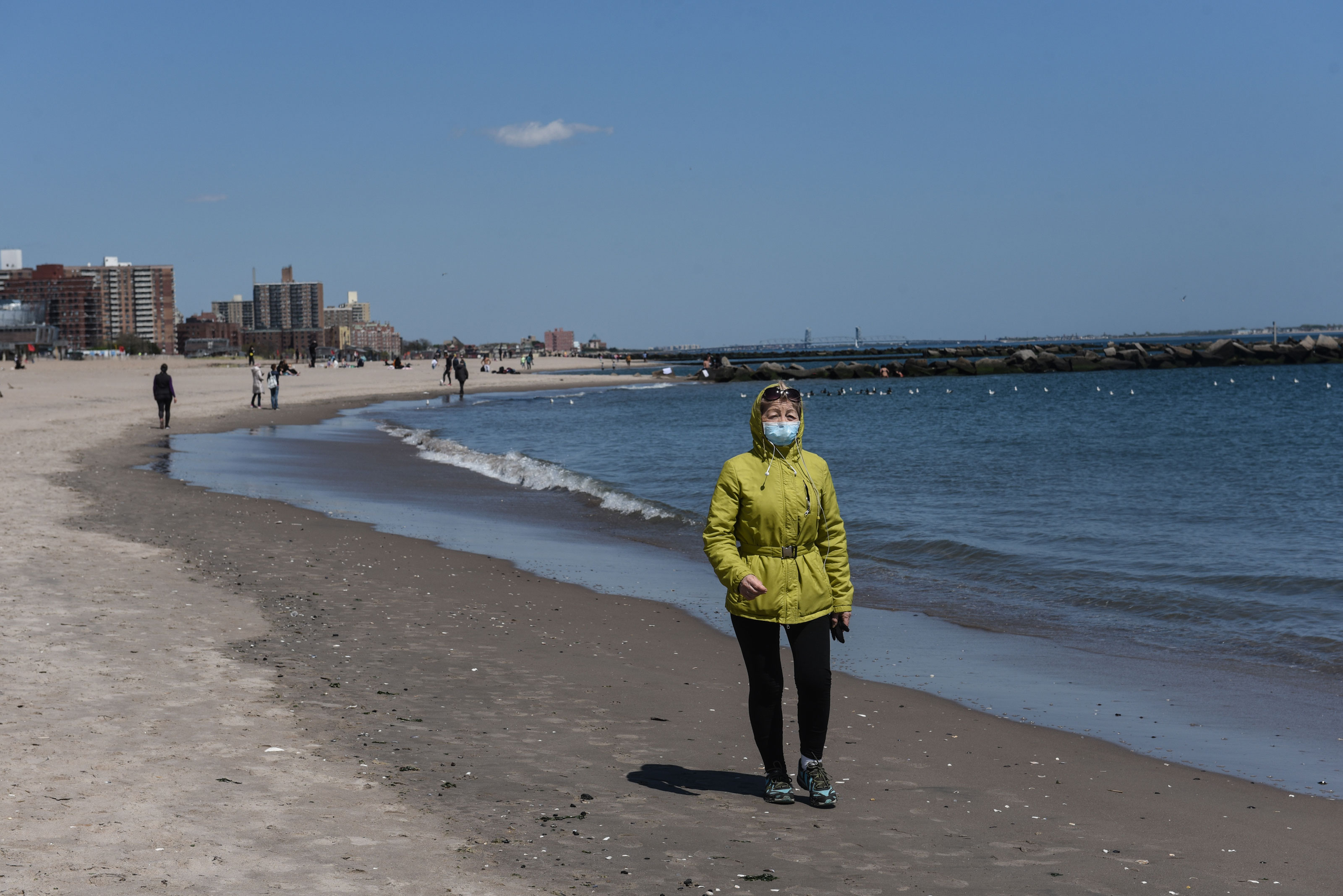 A person walks on the beach on May 13 in the Coney Island neighborhood in the Brooklyn borough in New York City.