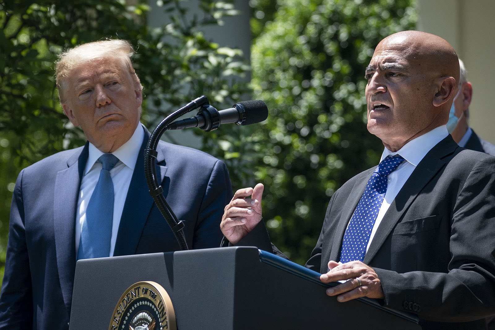 President Donald Trump listens as Moncef Slaoui, the former head of GlaxoSmithKlines vaccines division, speaks about coronavirus vaccine development in the Rose Garden of the White House on May 15, in Washington.