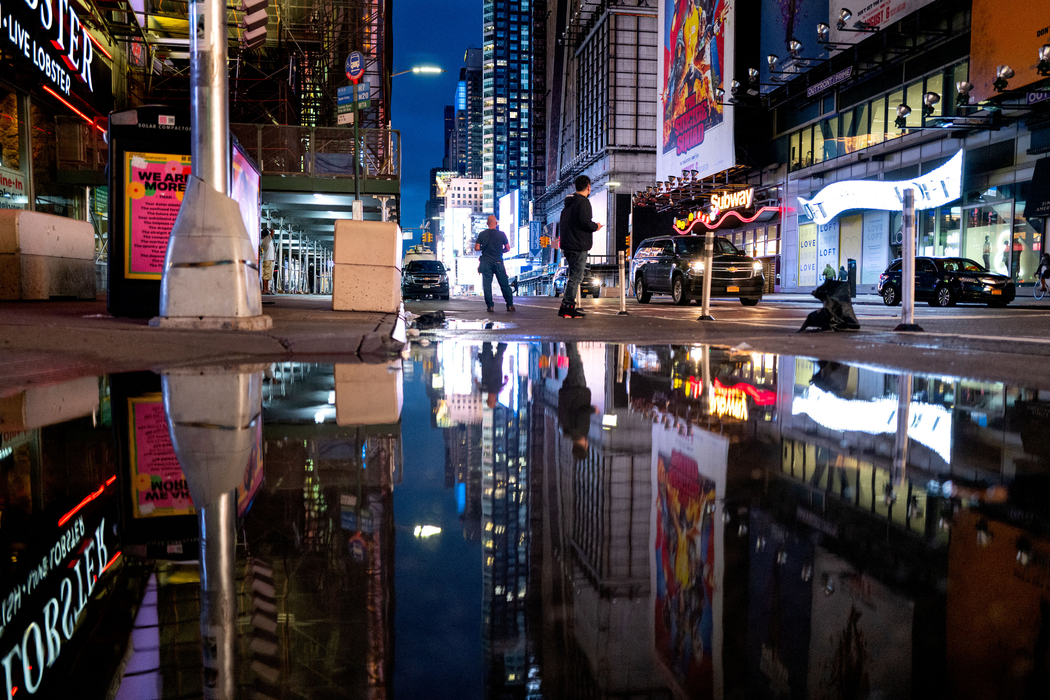 The lights of Times Square in New York are reflected in standing water on September 2.