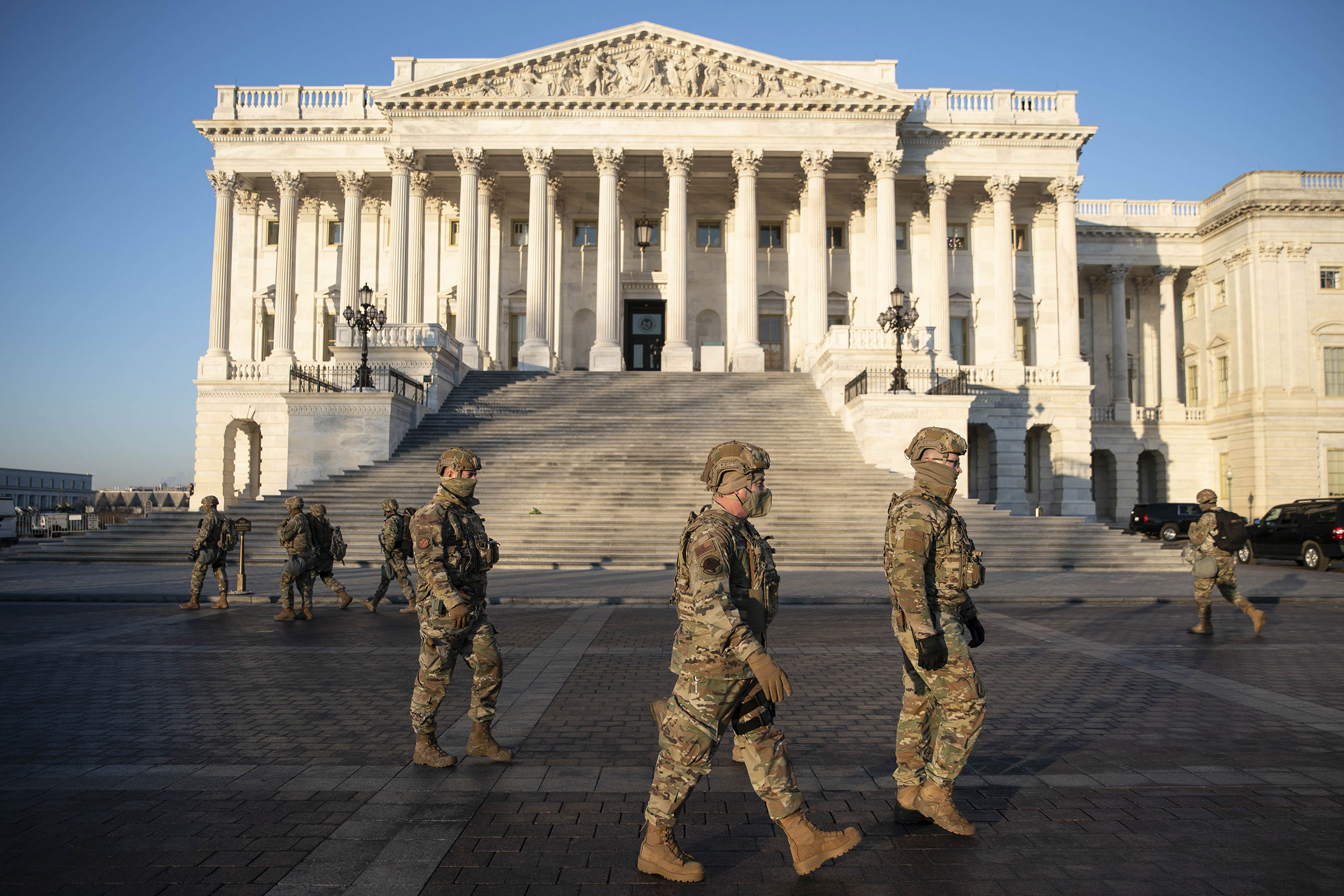Members of the National Guard walk outside the US Capitol on Wednesday, January 13.
