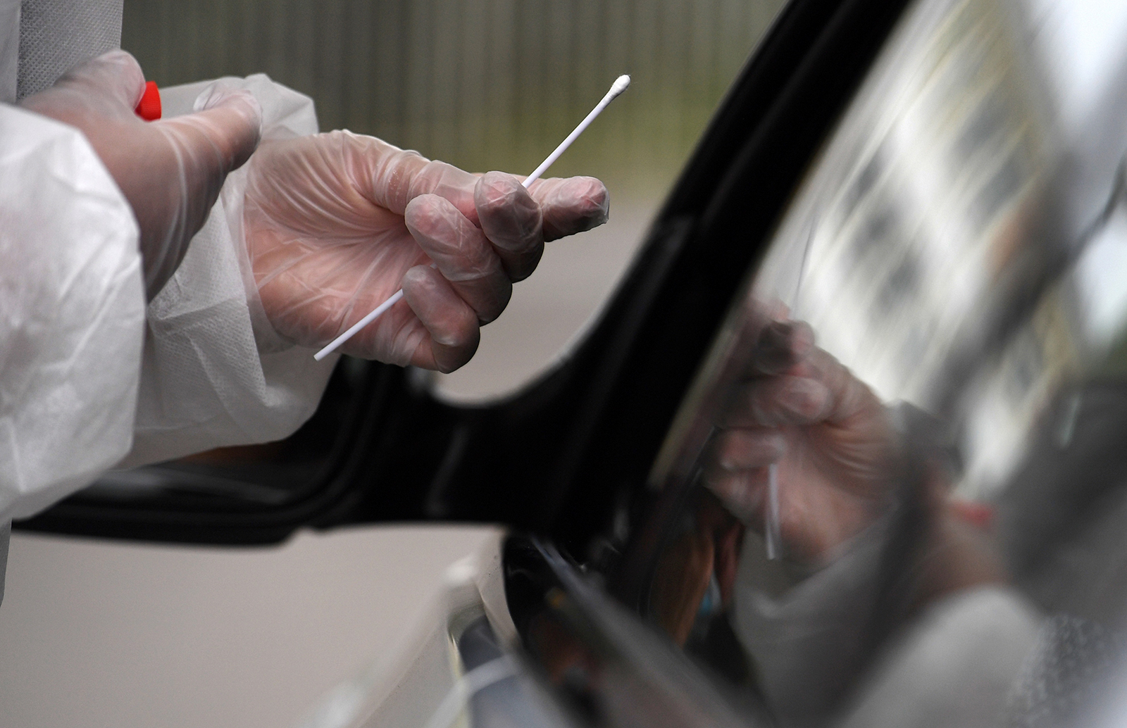 A member of medical staff holds a nasal swab as he collects samples from a person at a Covid-19 drive-in test in Brest, France, on Wednesday, July 31.