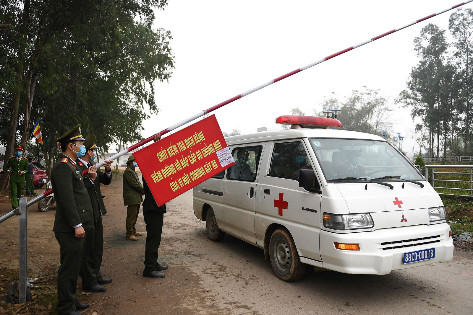 Police wearing face masks allow an ambulance to pass through a checkpoint at the Son Loi commune in Vinh Phuc province on February 13, 2020.