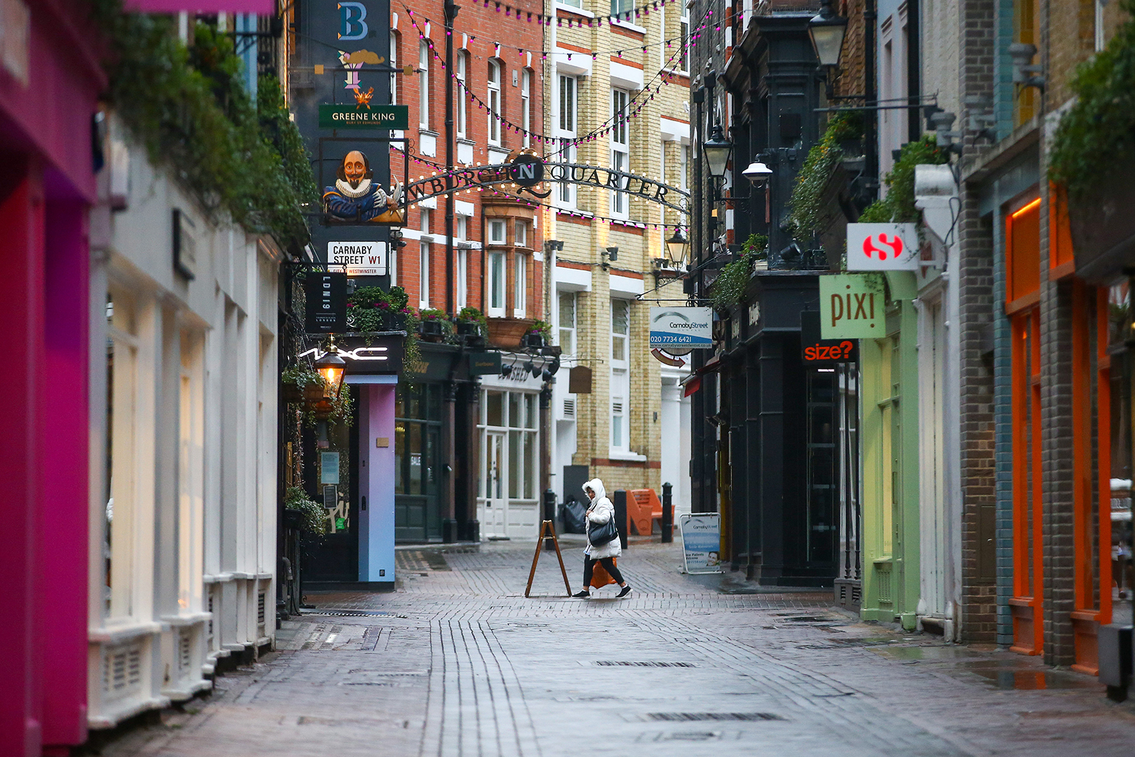 A pedestrian passes closed shops on Carnaby Street in London on Tuesday, January 5.