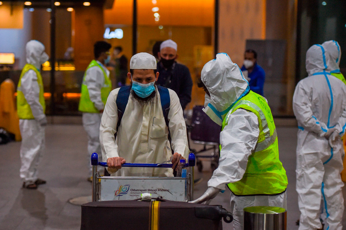 Health workers watch as passengers arrive at the Chhatrapati Shivaji International Airport from London on December 22.