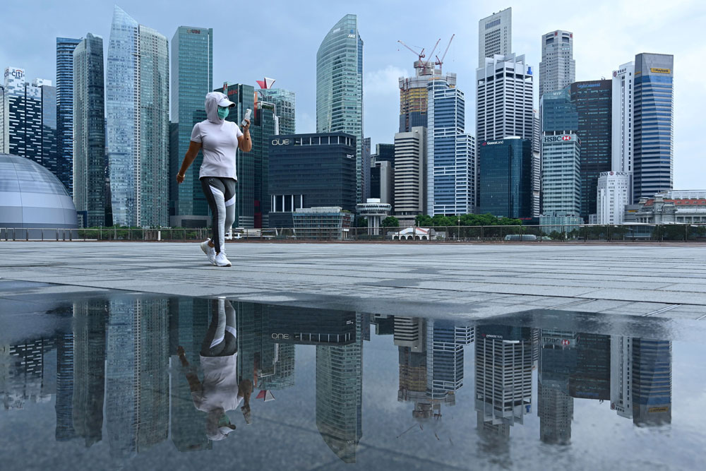 A woman wearing a face mask walks along a promenade in Singapore on May 4.