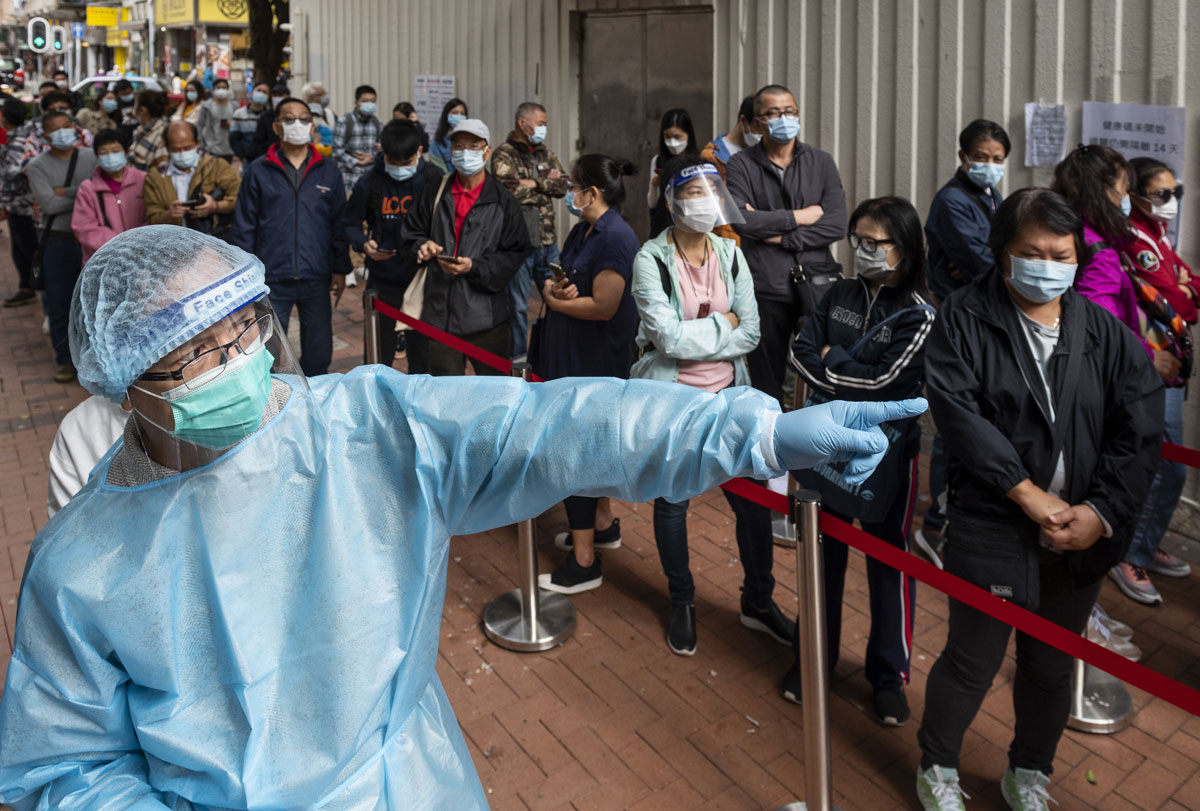 A health worker organizes the visitors' queue lines outside a Community Testing Centre in Hong Kong on Nov. 30.