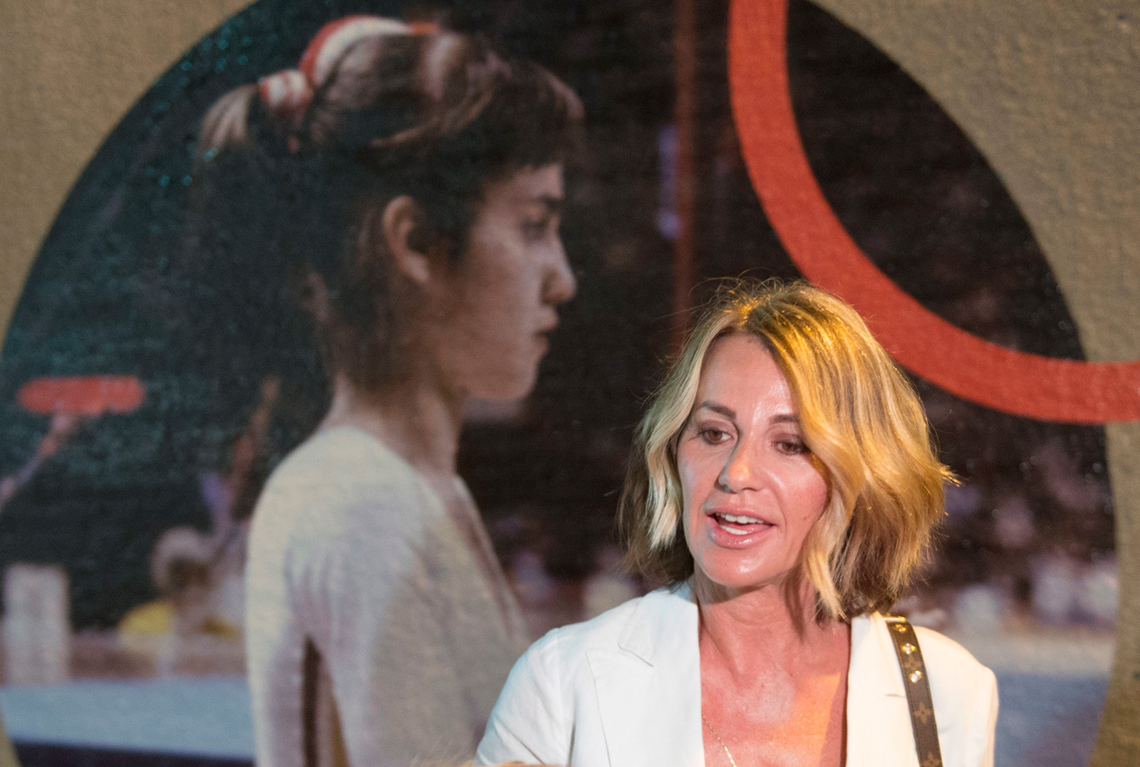 Montreal 1976 Olympics gymnastics champion Nadia Comaneci stands next to a photo of herself competing in this July 21, 2016, file photo.