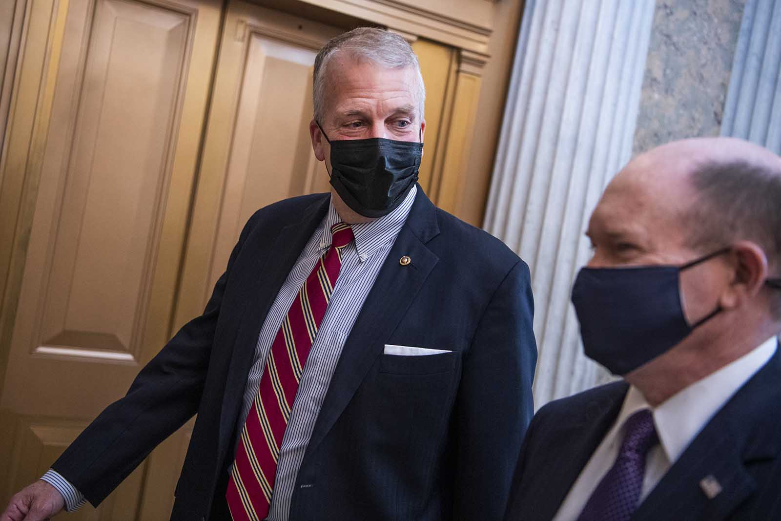 Sen. Dan Sullivan and Sen. Chris Coons are seen outside the chamber as the Senate votes to open debate on the coronavirus relief package on Thursday, March 4.