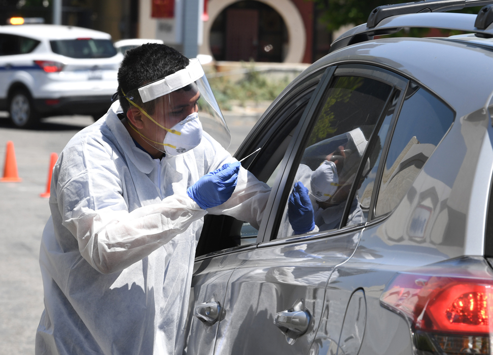 A worker wearing personal protective equipment performs drive-up Covid-19 testing administered from a car at Mend Urgent Care testing site for the novel coronavirus at the Westfield Fashion Square on May 13, in the Sherman Oaks neighborhood of Los Angeles, California.