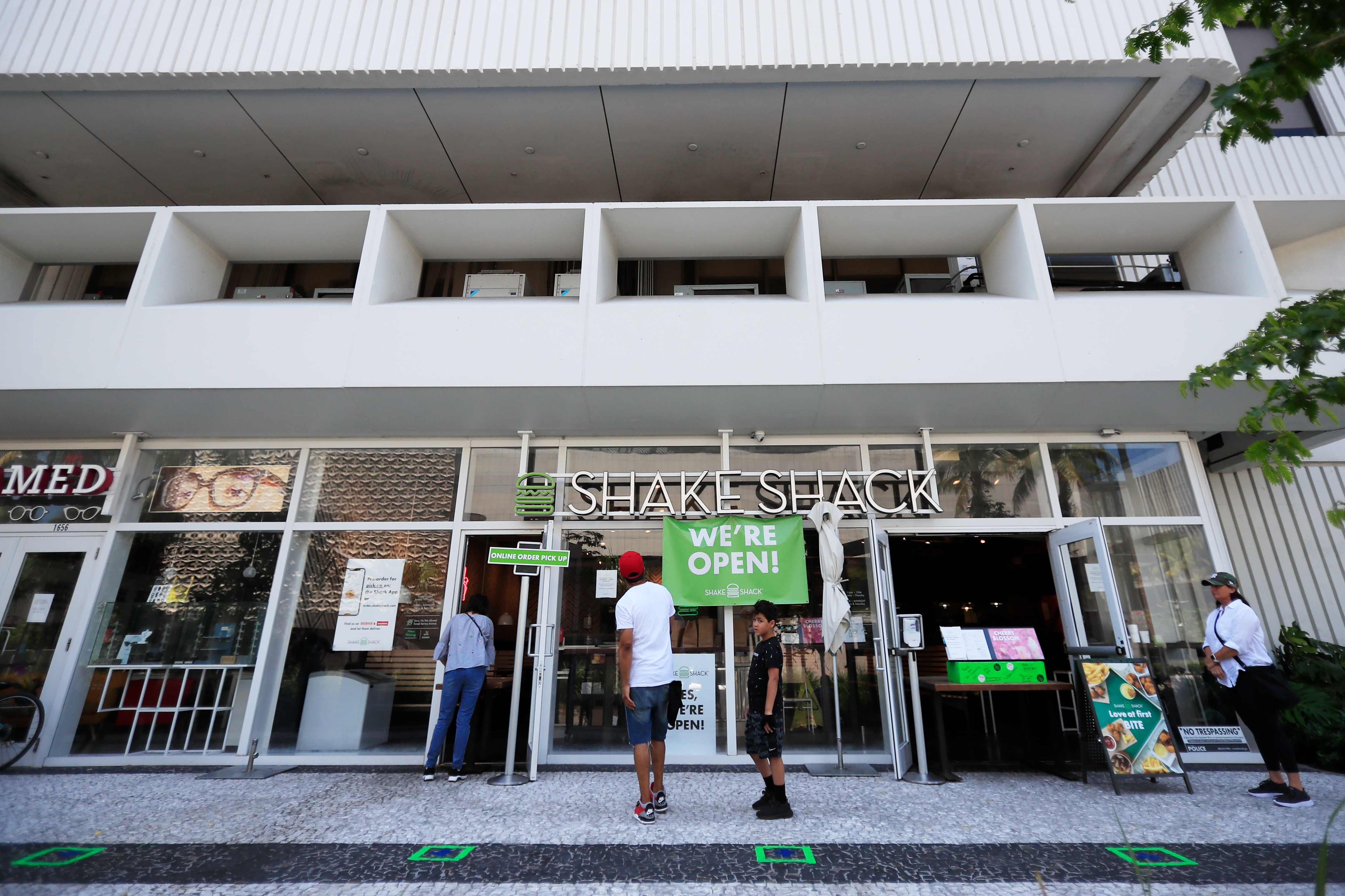 Customers wait for to-go orders outside Shake Shack in Miami Beach, Florida on April 19.