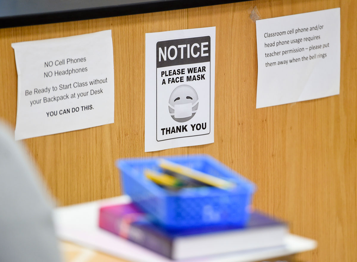 A sign in a classroom reminds students to wear face masks.