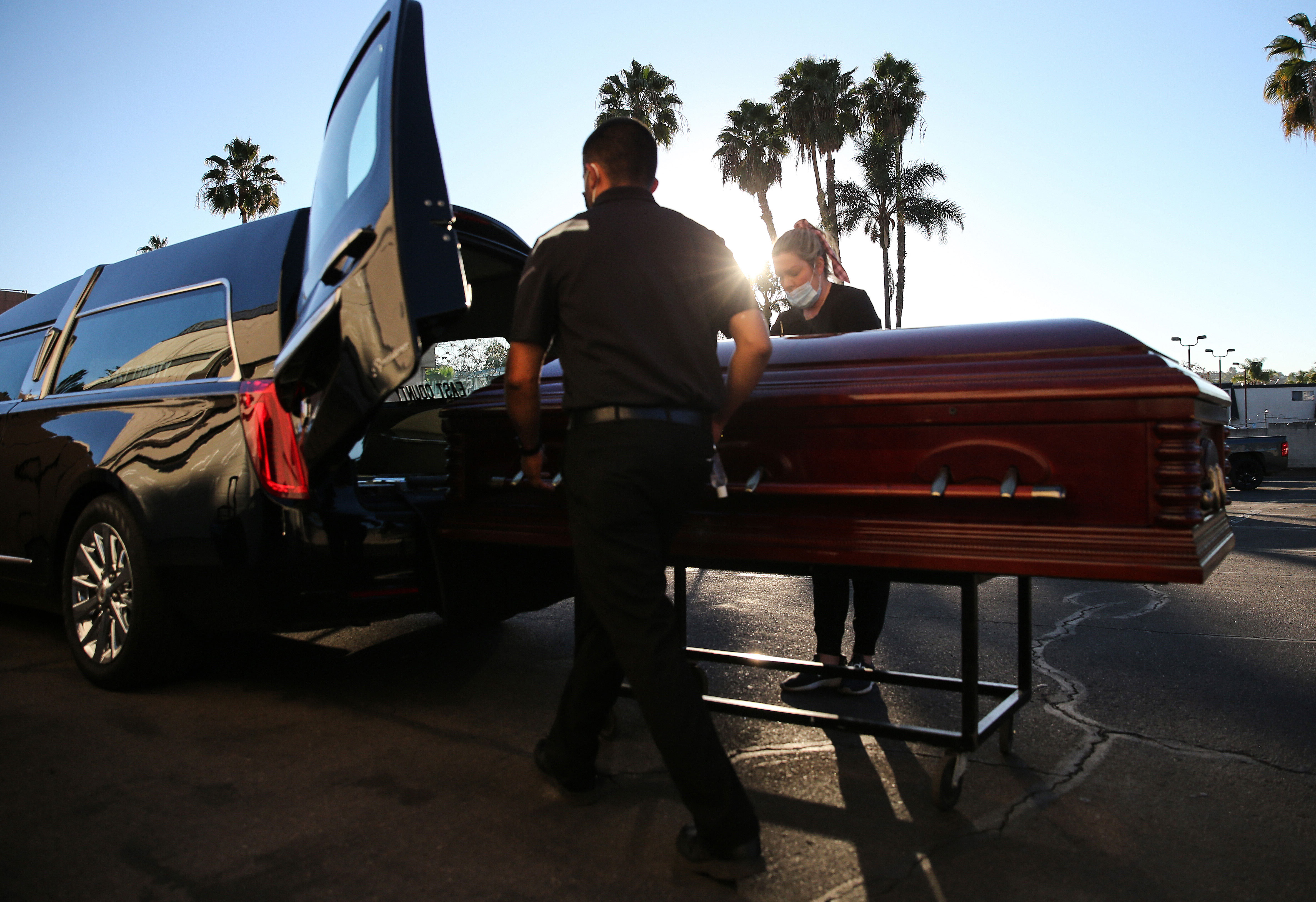 Embalmer and funeral director Kristy Oliver, right, and funeral attendant Sam Deras load into a hearse the casket of a person said to have died from Covid-19 at East County Mortuary in El Cajon, California, on January 15.