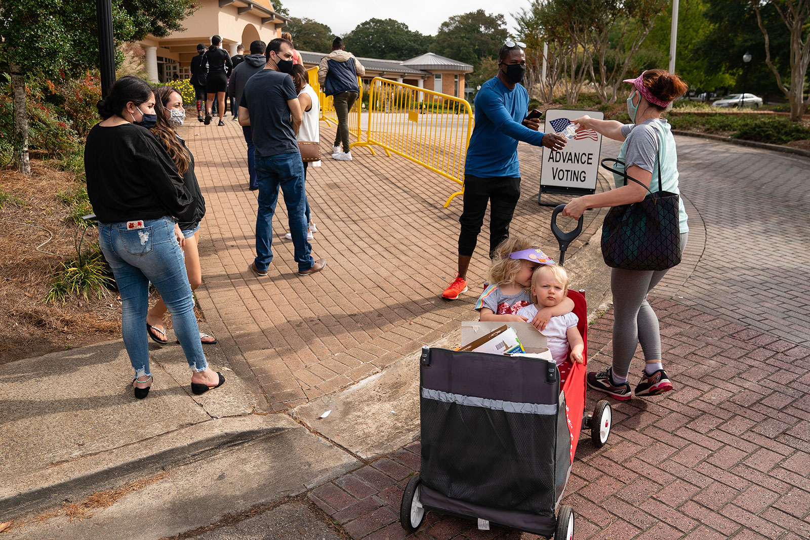 Megan Dominy, right, offers water and snacks to people waiting in line to vote in Smyrna, Georgia, in October 2020.