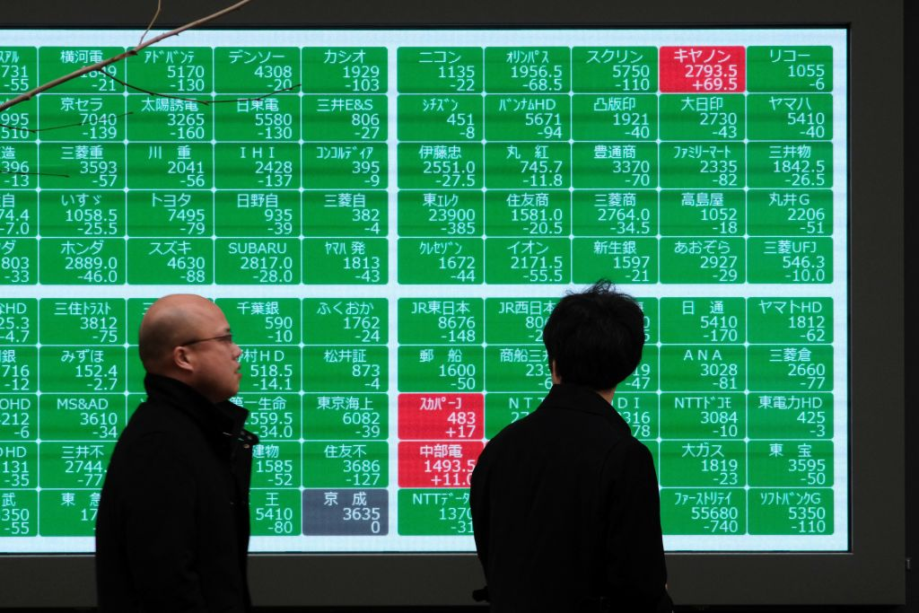 Pedestrians walk past a quotation board displaying numbers of the Nikkei 225 Index in Tokyo on Wednesday.