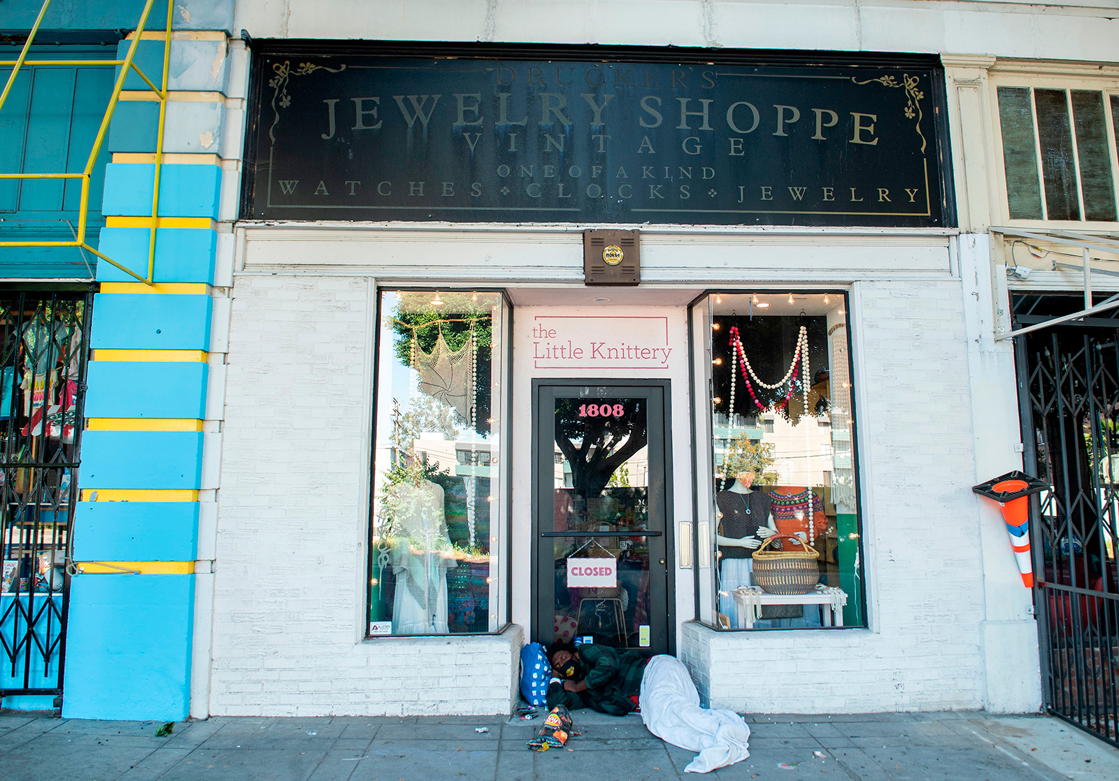 A homeless person wearing a mask sleeps in front of a store closed on May 8, in Los Angeles.