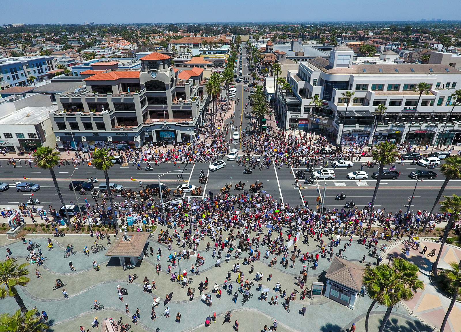 Thousands of people gather at the corner of Main Street and Pacific Coast Highway to protest coronavirus (COVID-19) closures in Huntington Beach, California on May 1.