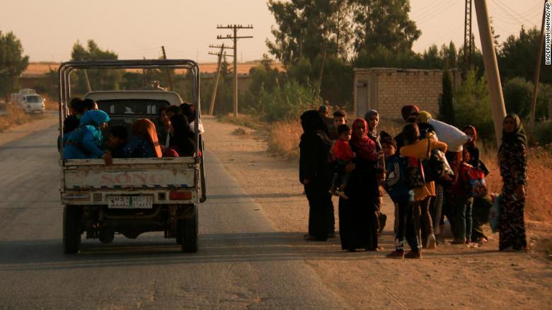 Syrians flee shelling by Turkish forces in Ras al-Ayn, northeast Syria.