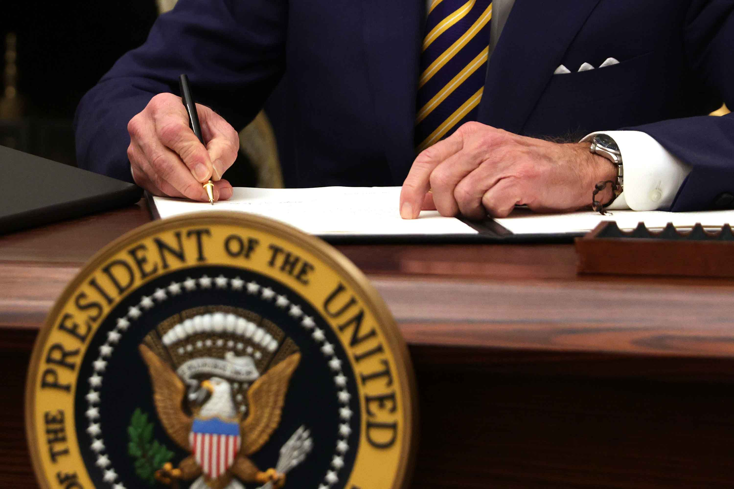 President Biden signs an executive order during an event on economic crisis at the White House in Washington, DC on January 22.