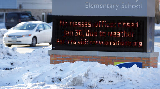 A car passes an elementary school closed due to cold weather on Wednesday in Des Moines, Iowa.