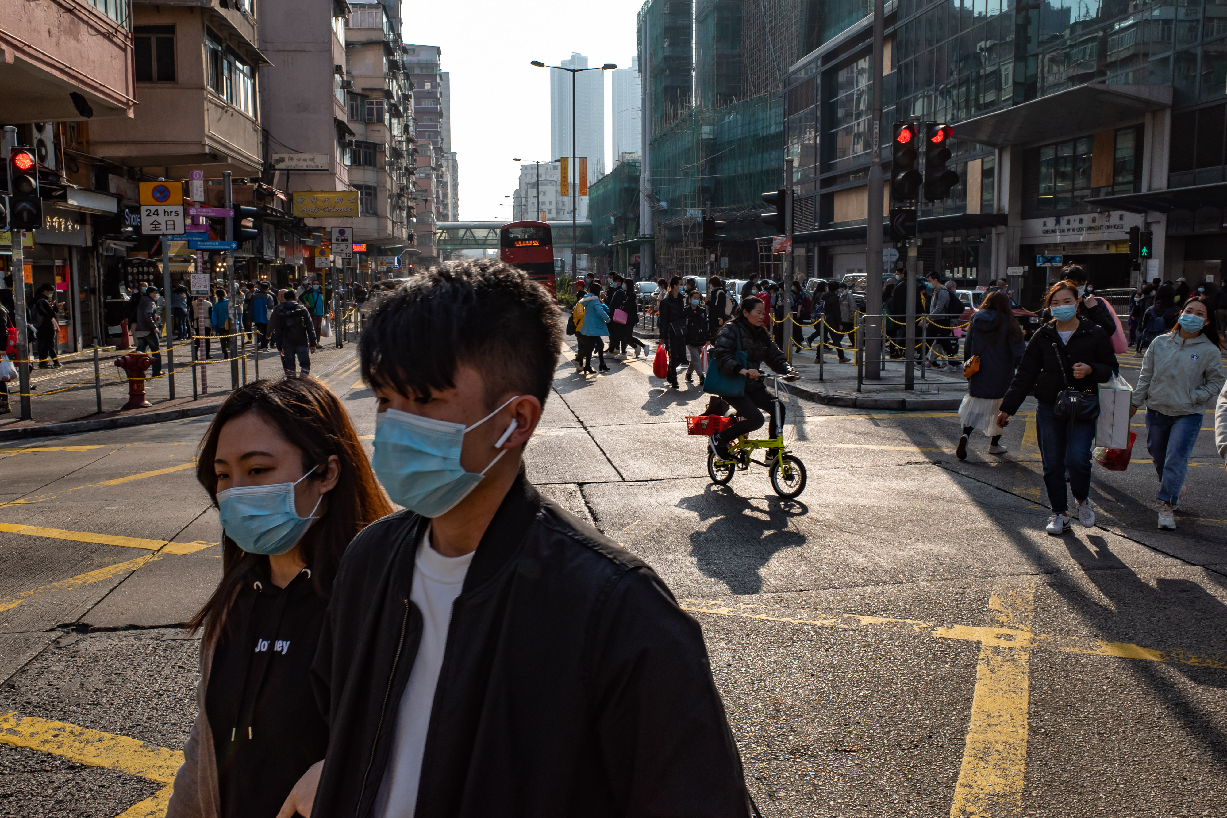 People wearing face masks cross an intersection at a shopping district on Saturday in Hong Kong.