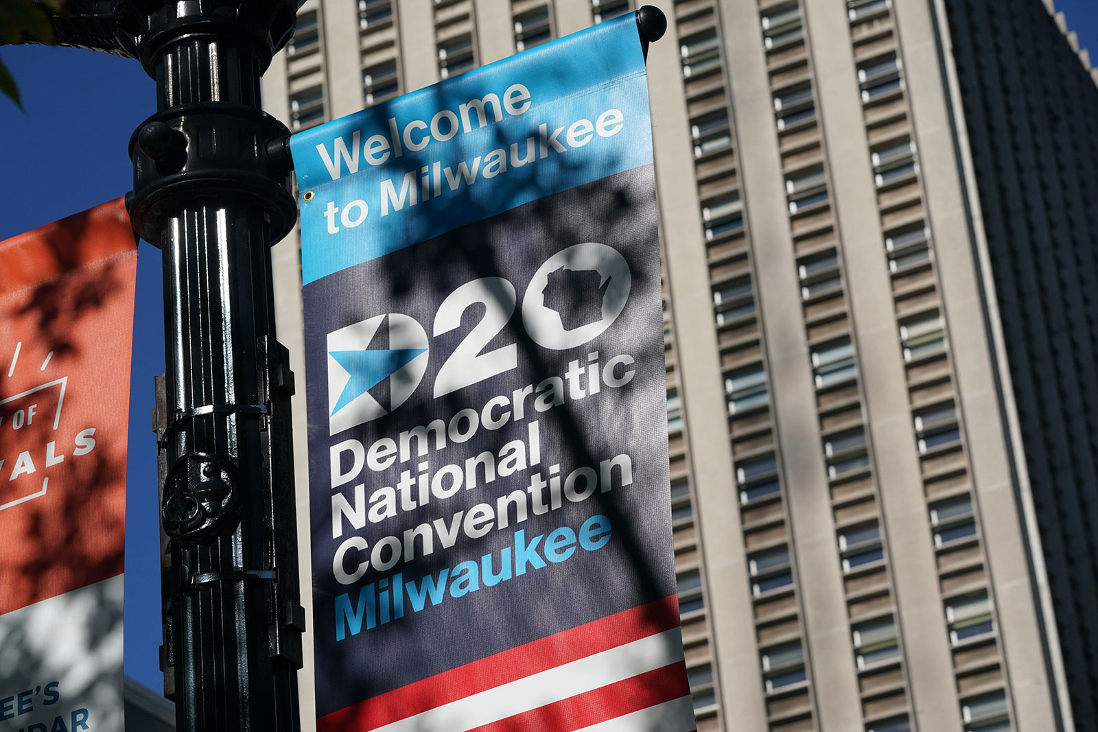 A sign advertises the Democratic National Convention in Milwaukee. The speaker list for the convention has been scaled back significantly after the coronavirus forced Democratic planners to scrap plans for an in-person event in Milwaukee and shrink most of the live programming totwo hours each night from 9 p.m. ET to 11 p.m. ET.