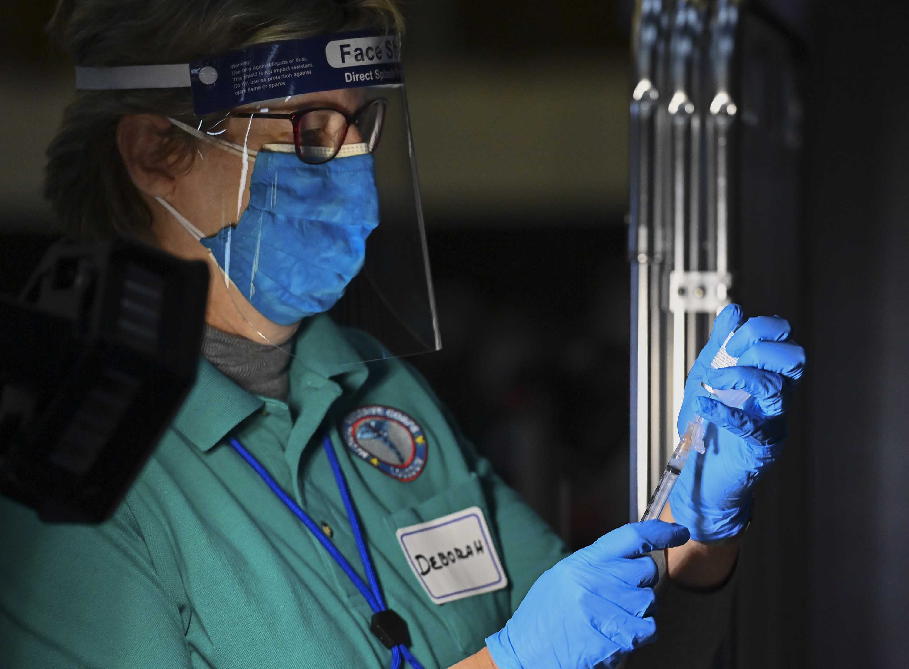 Nurse Deborah Henley fills a syringe with the Moderna Covid vaccine as first responders are vaccinated on December 28, in Sterling, Virginia.