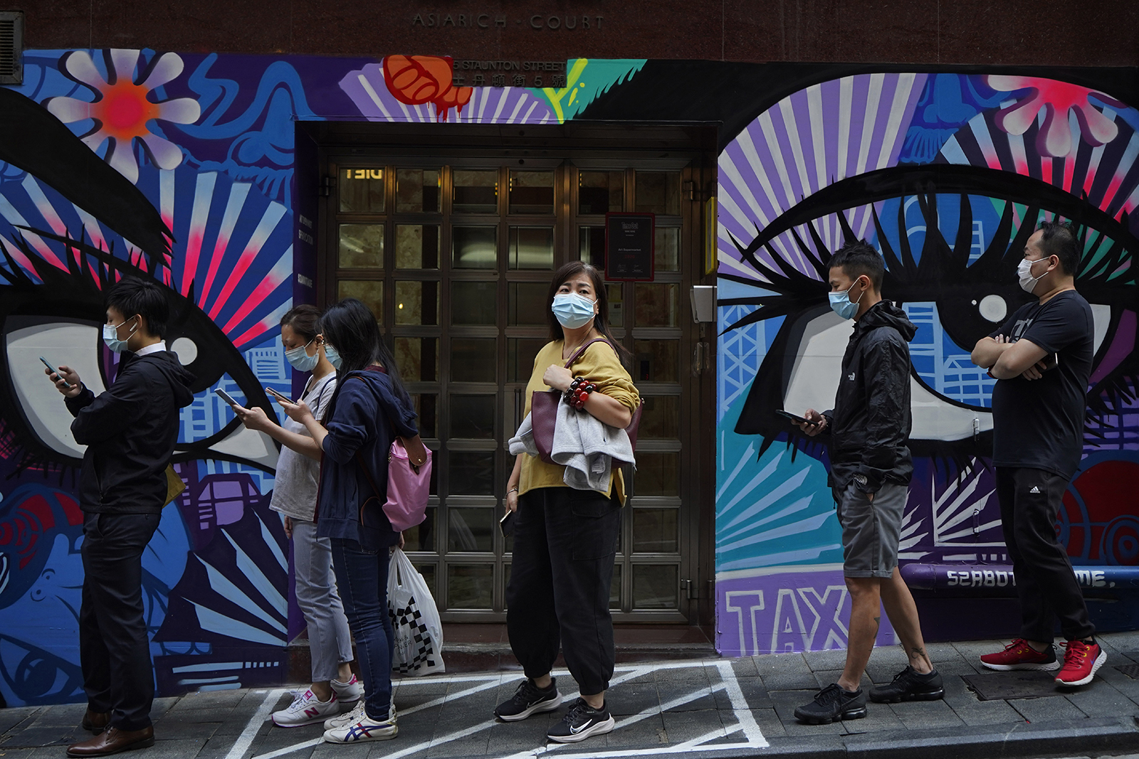 People wearing face masks to help curb the spread of the coronavirus wait outside a bakery in Hong Kong on Monday, Nov. 30.