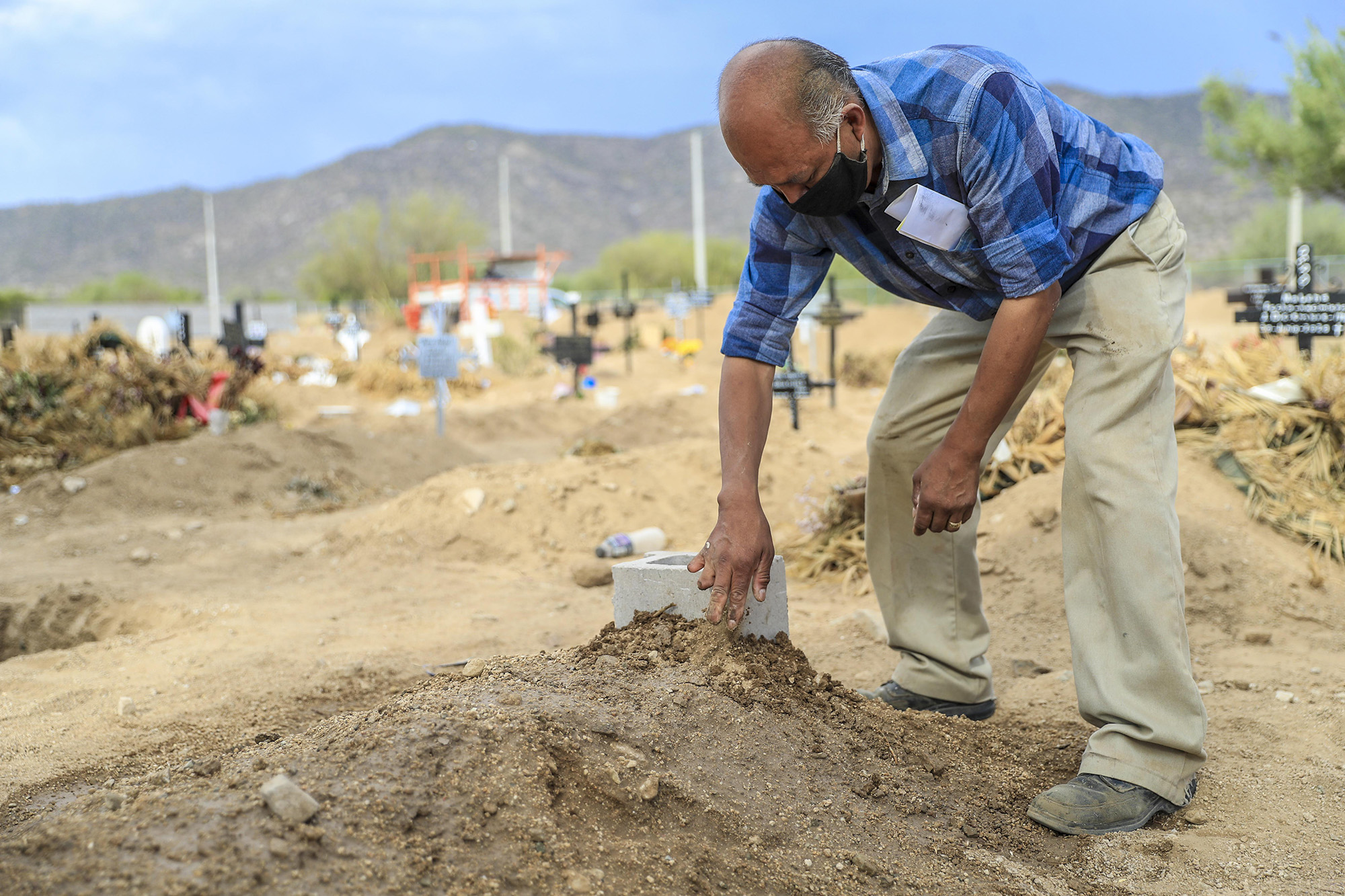 Juan Hernández waters the grave of his brother Mario who died of COVID-19 on July 16, in Hermosillo, Mexico.