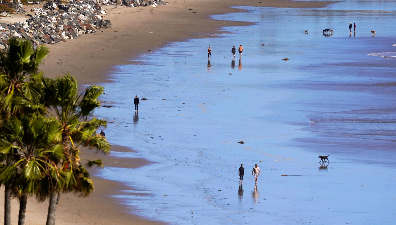 People walks along Zuma Beach, March 23, in Malibu, California.