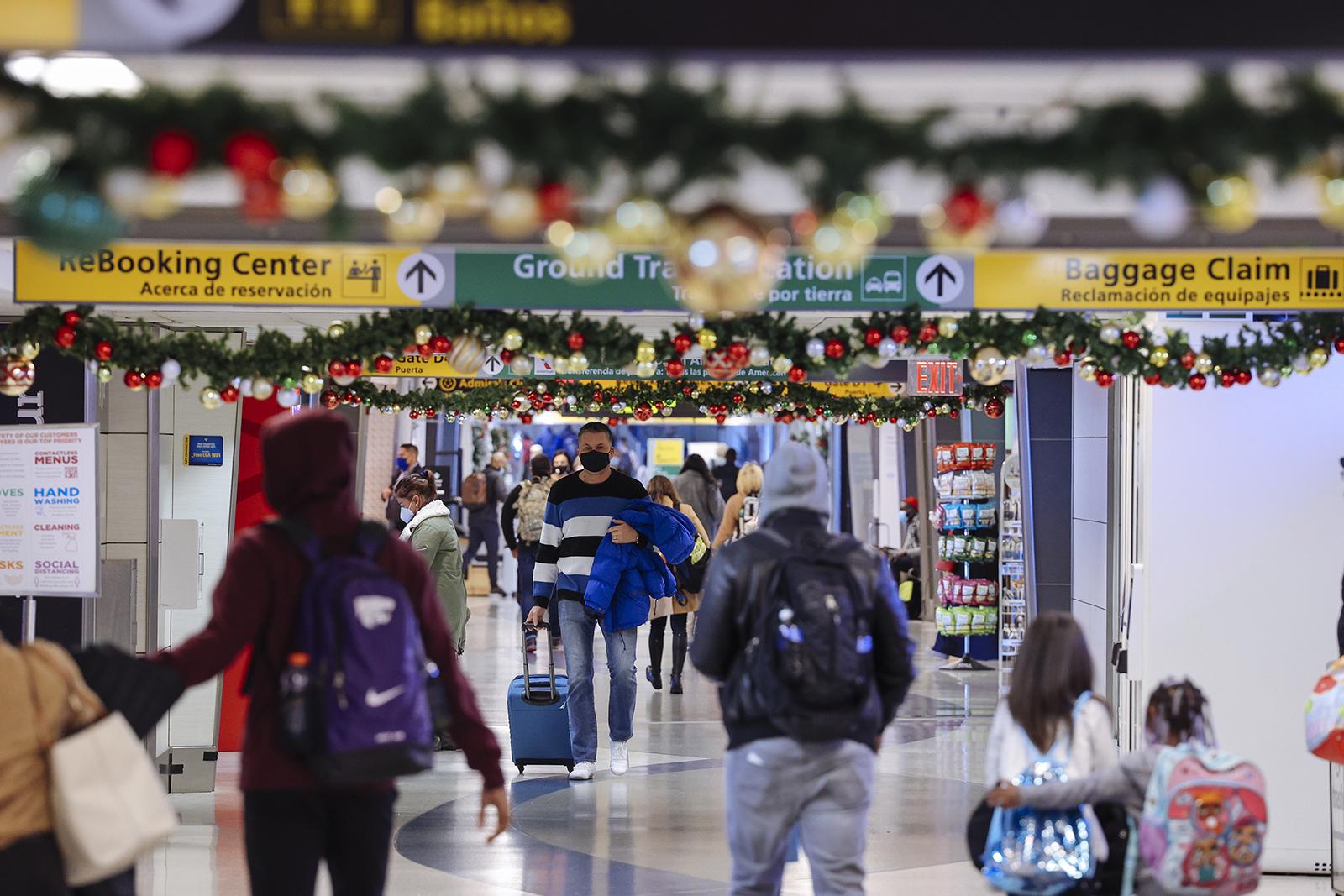 Travelers wearing protective masks walk through LaGuardia Airport (LGA) in New York, on  December 24.