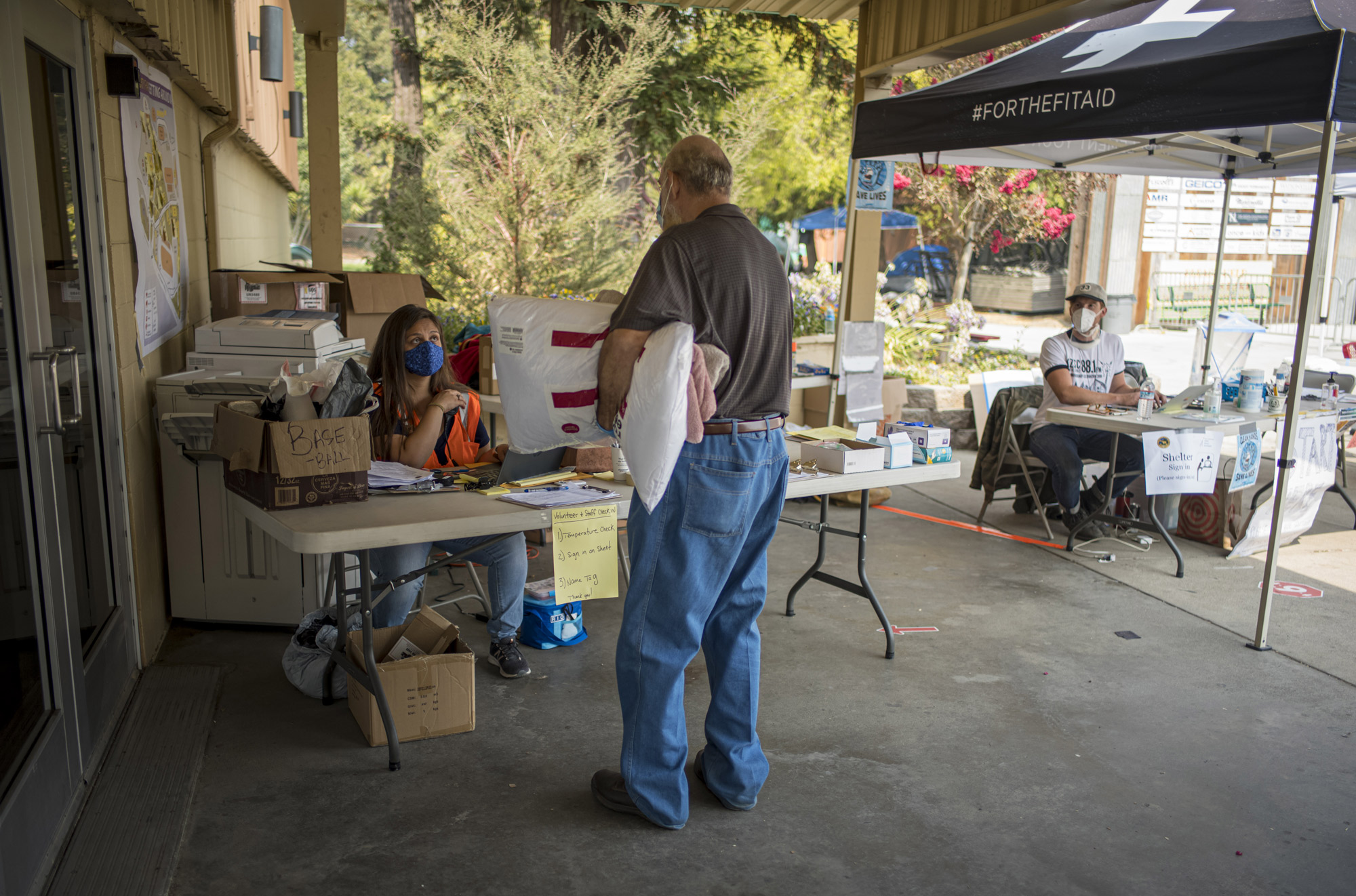 A volunteer checks-in an evacuee at an evacuation center at the Watsonville Fairgrounds in Watsonville, California, on August 26.