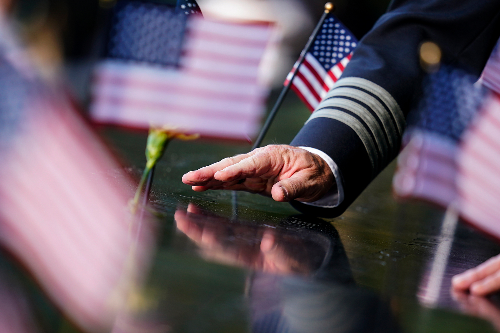 A person touches an inscribed name at the National September 11 Memorial and Museum ahead of the 20th anniversary of the 9/11 terrorist attacks, Friday, Sept. 10, 2021, in New York.