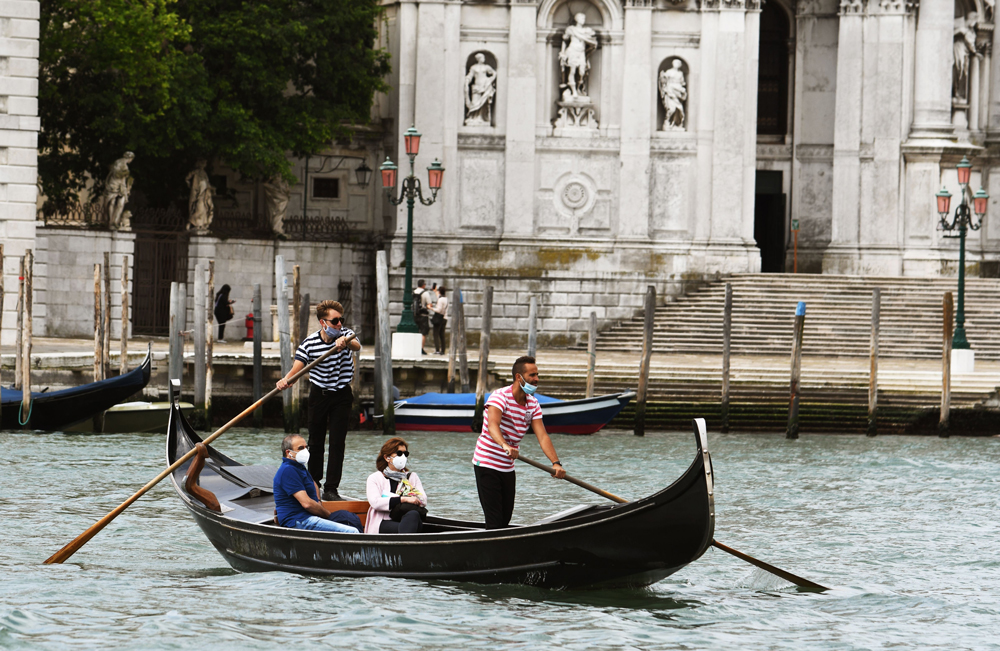 People enjoy a gondola ride on May 30 in Venice, Italy.