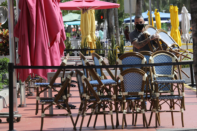 An employee at the Clevelander bar and restaurant on Ocean Drive stacks chairs after they shut down due to public health concerns caused by COVID-19 on Monday, July 13, 2020, in Miami Beach, Florida.