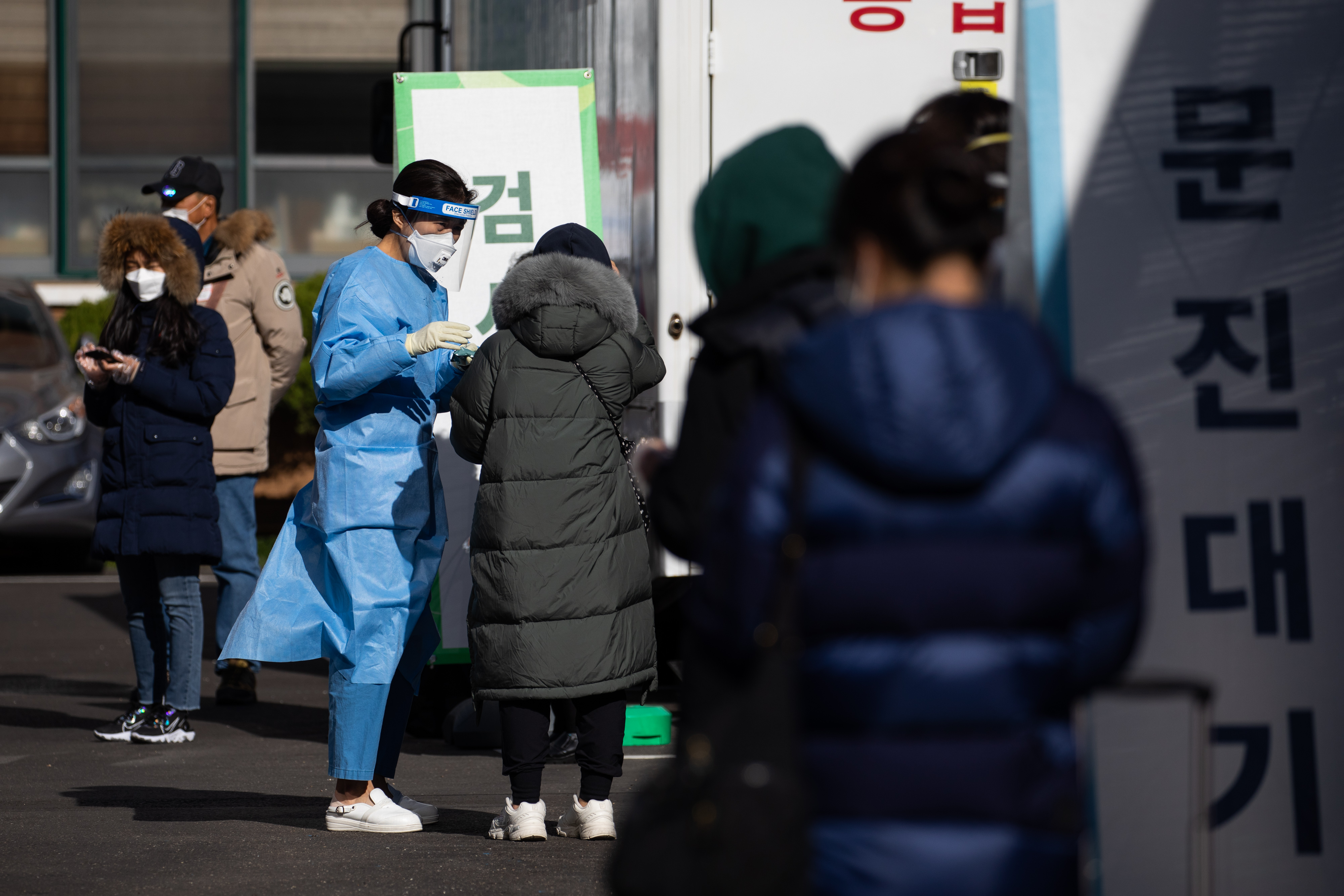 A medical worker talks to a person waiting in line at a Covid-19 testing station in Seoul, South Korea, on Saturday, November 28.