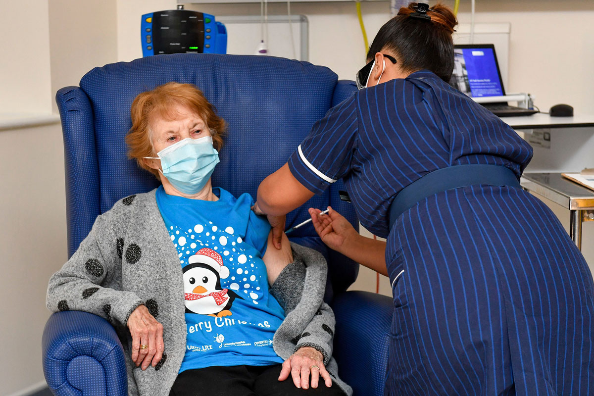 Margaret Keenan, the first patient in the UK to receive the Pfizer-BioNTech Covid-19 vaccine, receives a shot at University Hospital in Coventry, England on Dec. 8.