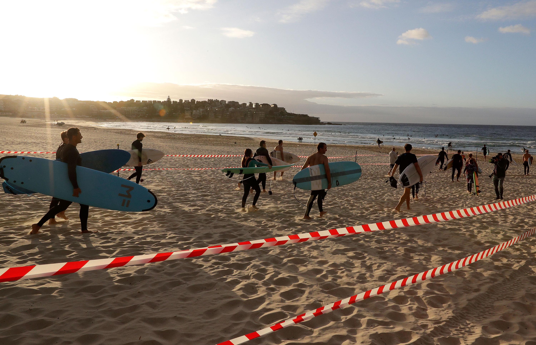 Surfers arrive at Bondi Beach in Sydney, Australia, on April 28.
