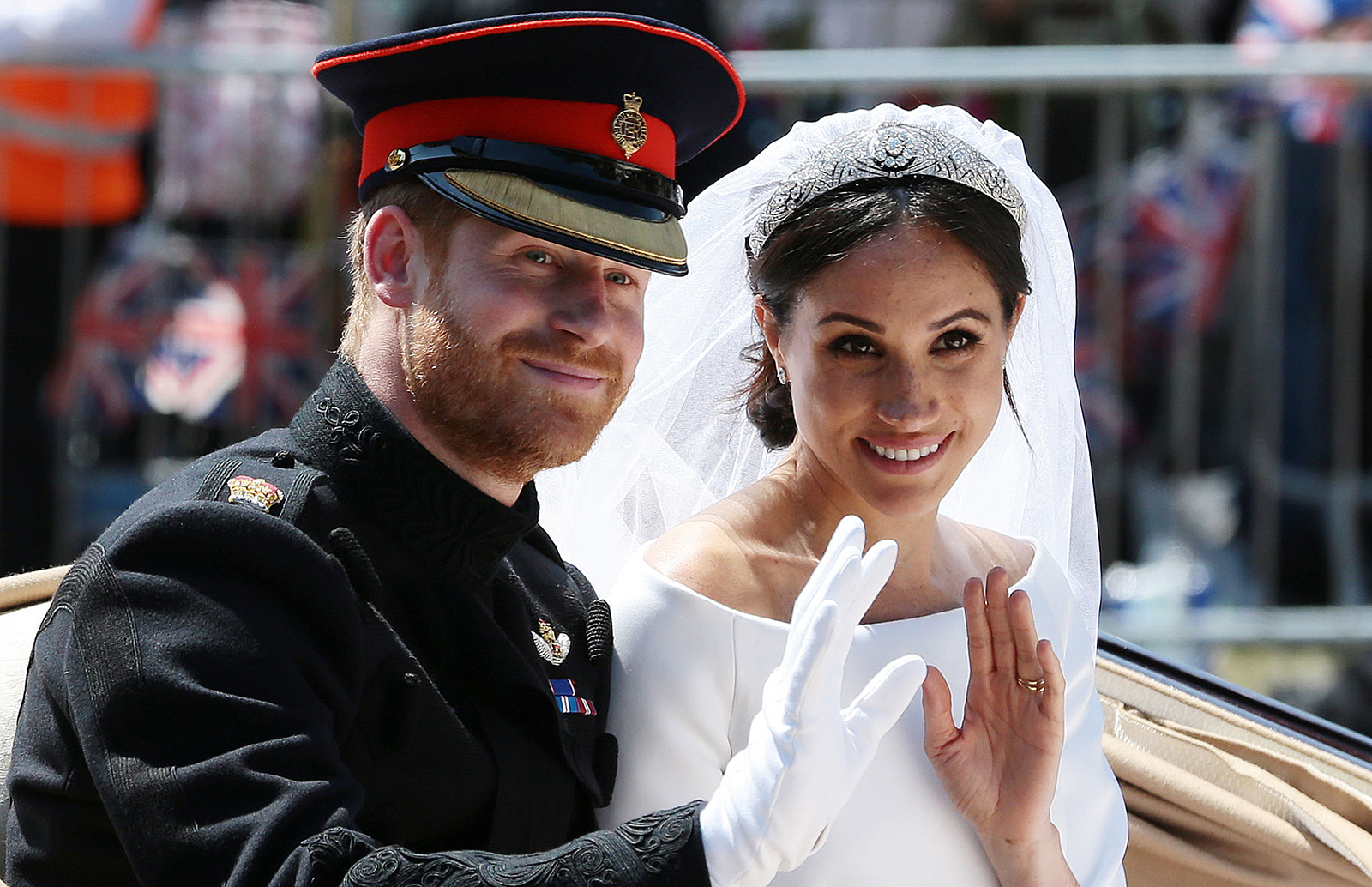 Britain's Prince Harry, Duke of Sussex and his wife Meghan, Duchess of Sussex wave from the Ascot Landau Carriage during their carriage procession on the Long Walk as they head back towards Windsor Castle in Windsor, on May 19, 2018 after their wedding ceremony.