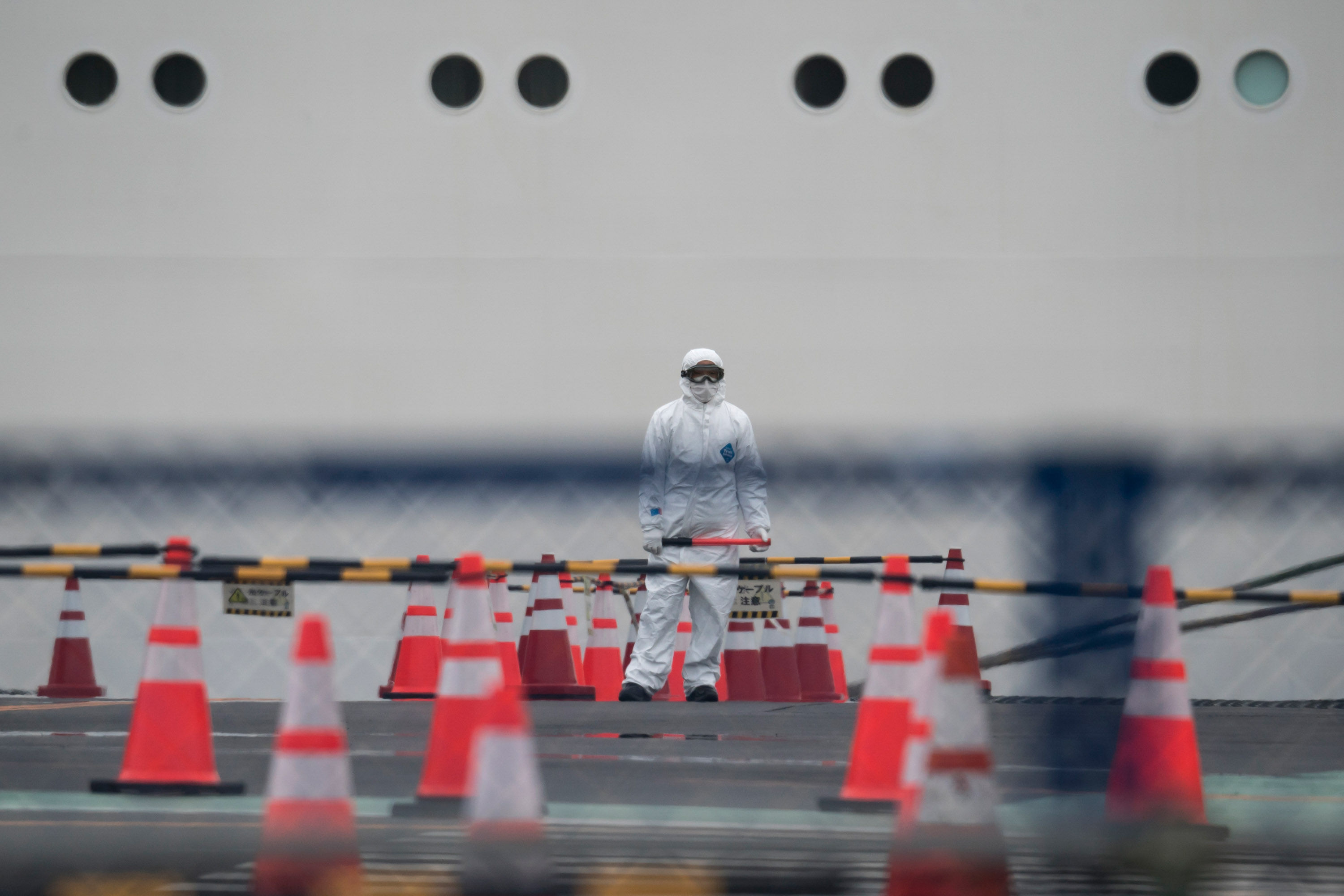 A worker wears a protective suit in front of the quarantined Diamond Princess cruise ship in Yokohama, Japan on Thursday.