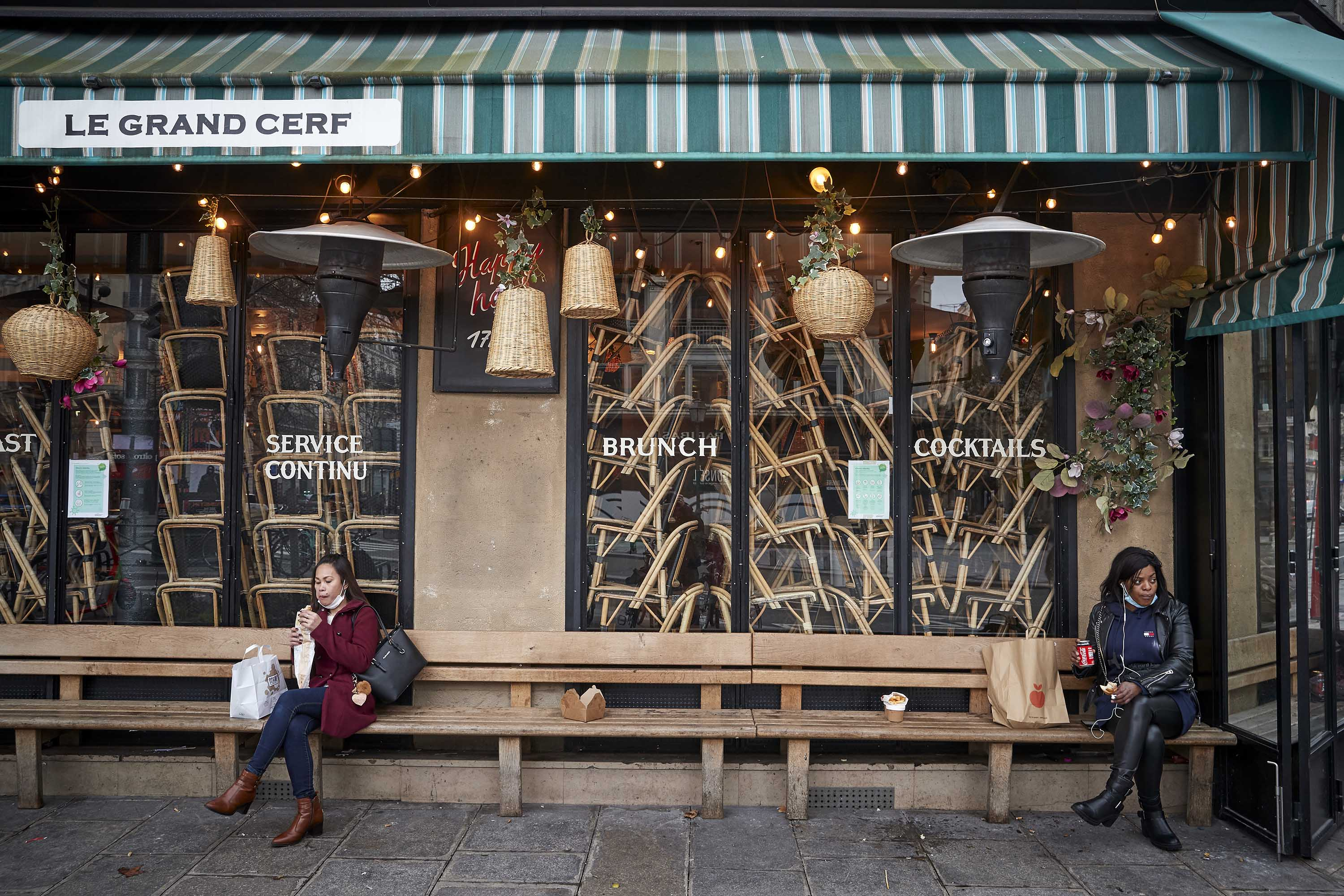 People eat their lunches outside a closed restaurant in Paris on February 1.