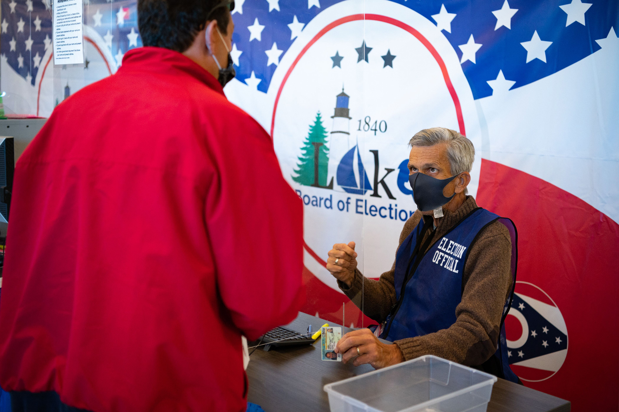 Election official Scott Hagara checks in a voter at the board of elections headquarters during early voting on October 16 in Painesville, Ohio.