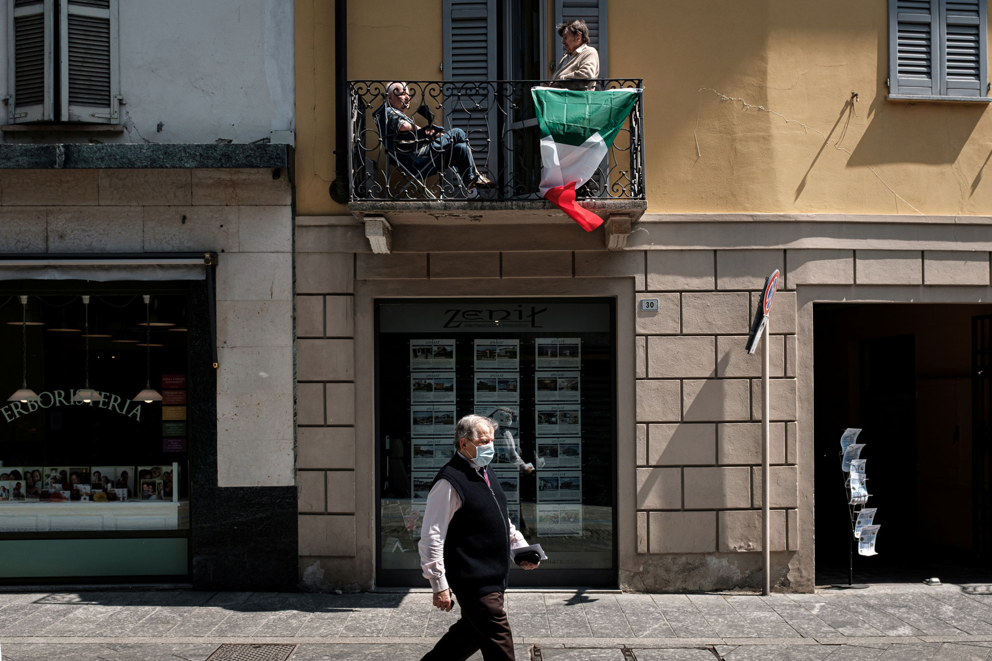 People enjoy the sun from a balcony in Codogno, Italy, on May 4.