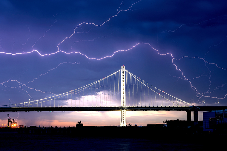 Lightning forks seen over the San Francisco-Oakland Bay Bridge as a storm passes over Oakland, California on Sunday on August 16, 2020. Numerous lightning strikes early Sunday sparked brush fires throughout the region.