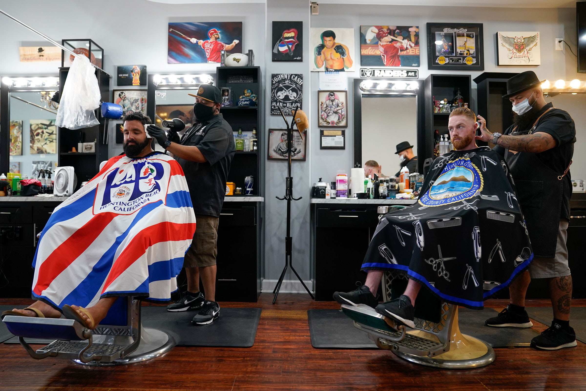 Ricardo Rivera, left, has his hair cut Wednesday by Anthony Acosta while Braunson McDonald has his hair cut by Luis Lopez in Huntington Beach, California.