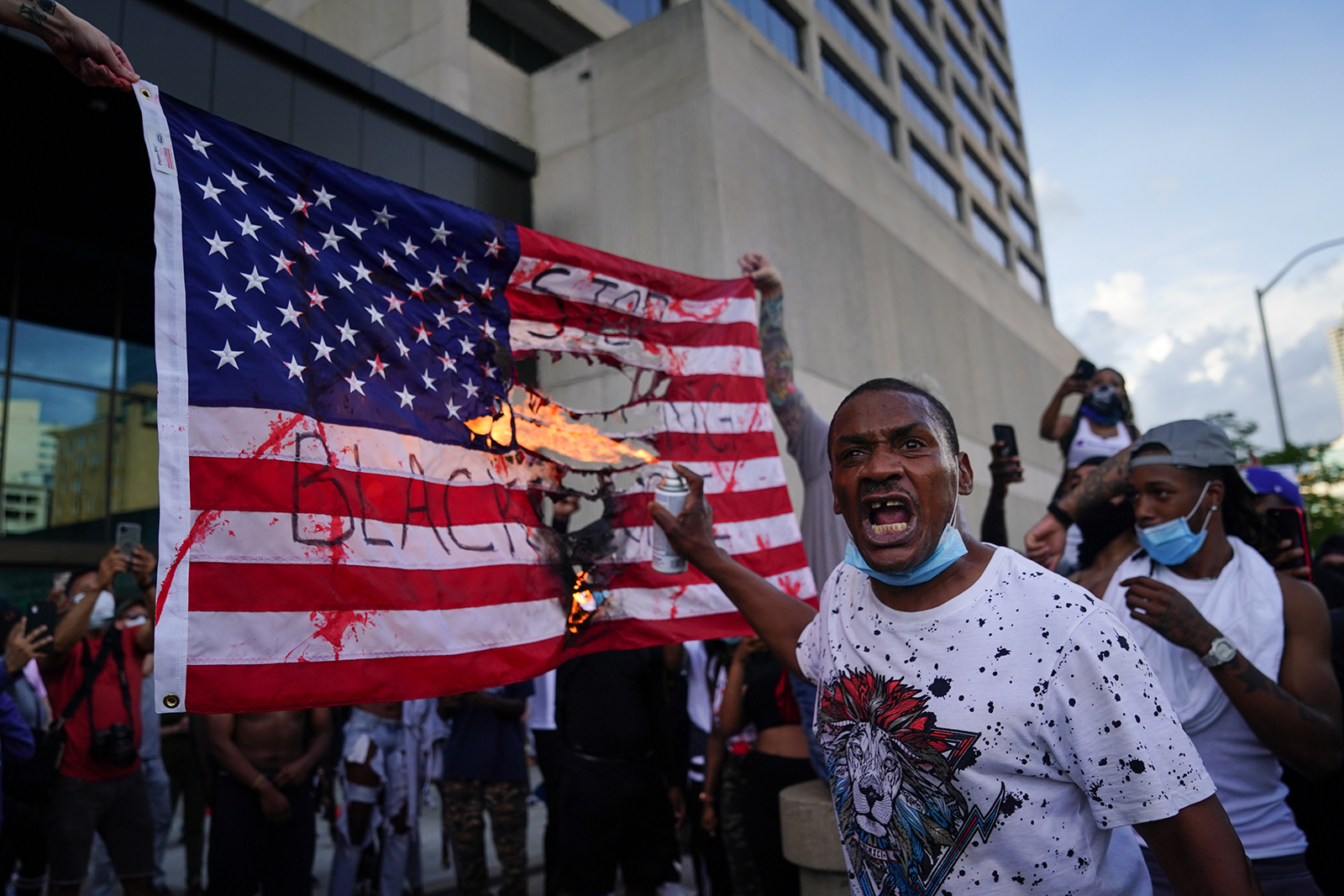 Protesters burn a flag outside the CNN Center on May 29, in Atlanta, Georgia.
