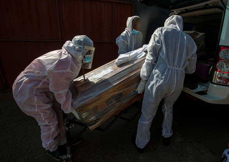 Funeral home workers in protective suits carry the coffin of a woman who died from COVID-19 into a hearse in Katlehong, South Africa, Tuesday, July 21.