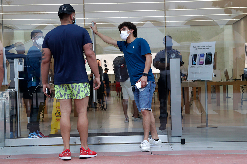 An employee wearing a protective face covering, right, monitors the flow of customers at an Apple retail store along Lincoln Road Mall during the new coronavirus pandemic on Wednesday, June 17, in Miami Beach.