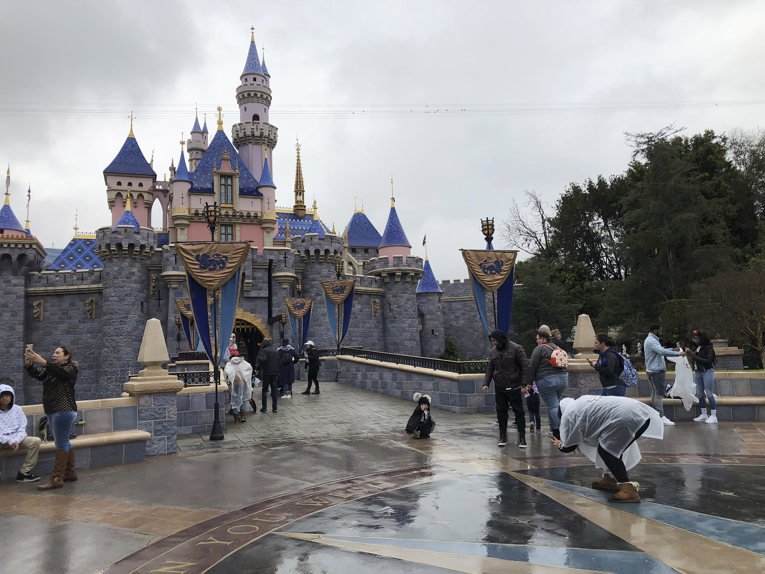 Visitors take photos at Disneyland in Anaheim, California, on Friday, March 13.