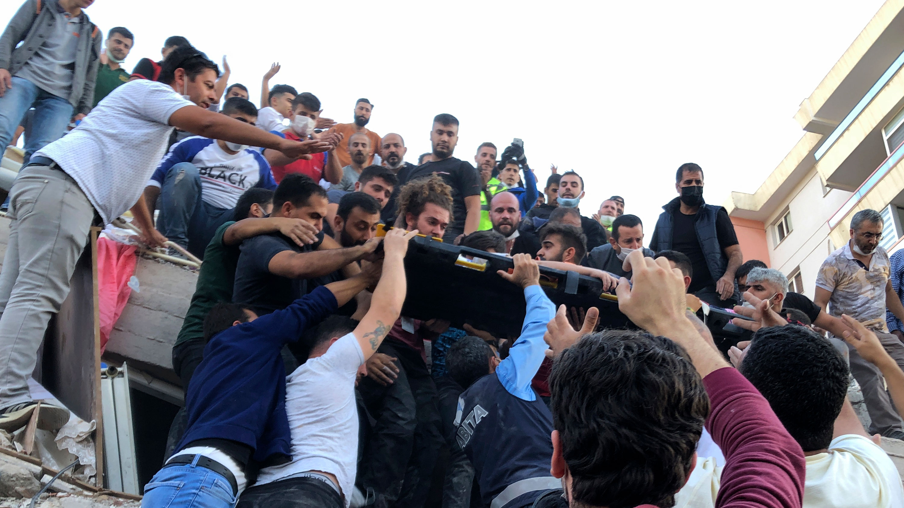 People carry a wounded person from the debris of a collapsed building in Izmir, Turkey, on October 30.